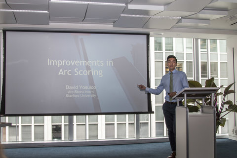 "David Yosuico leads a presentation at a lectern in front of a large screen. The presentation is titled ""Improvements in Arc Scoring."""